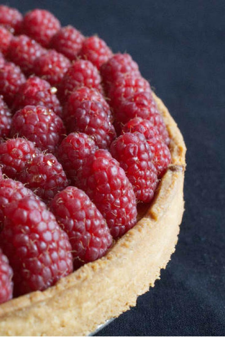 Delicious raspberry tart made up of a buttery shortcrust pastry, an almond cream, and fresh raspberries. The additional layer of raspberry jam helps settle the raspberries but also gives them additional flavor. #raspberry | nathaliebakes.com