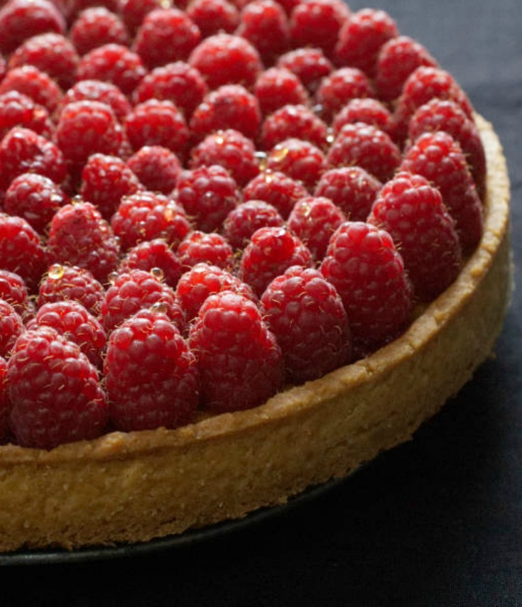 Delicious raspberry tart made up of a buttery shortcrust pastry, an almond cream and fresh raspberries. The additional layer of raspberry jam helps settle the raspberries but also gives them additional flavour. #raspberry | nathaliebakes.com