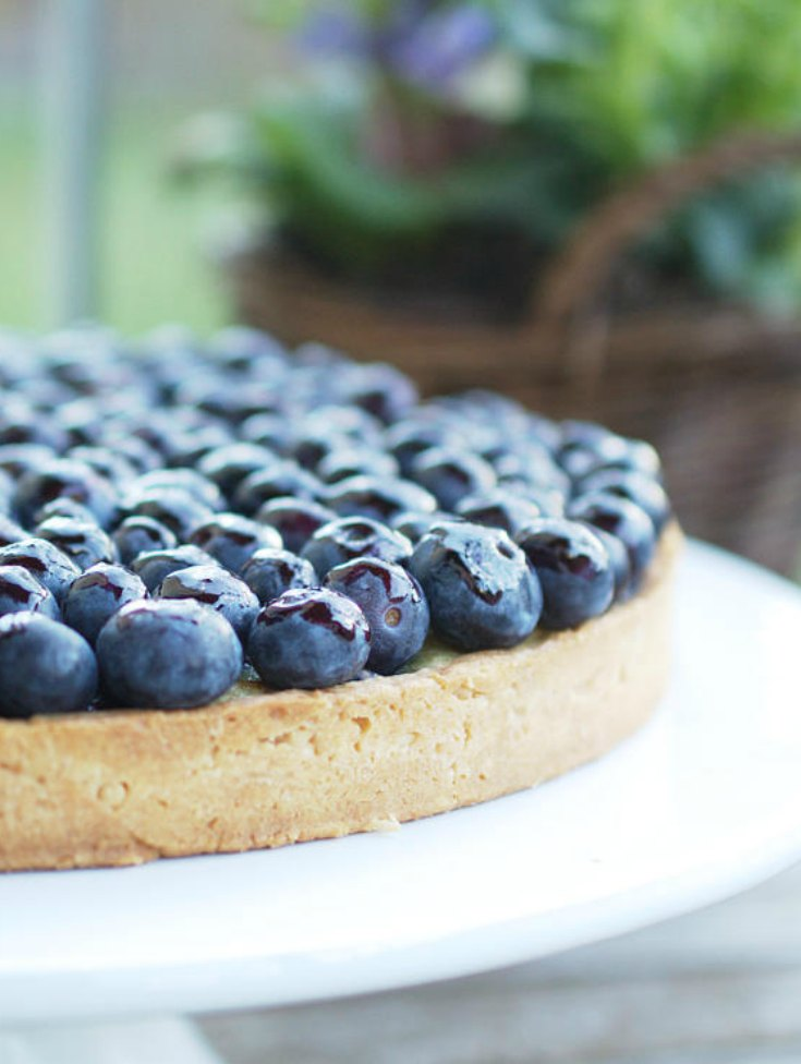 This blueberry tart is packed full of flavours and textures: the shortcrust pastry case is sprinkled with speculoos (or graham crackers) breadcrumbs and topped with blueberries two-ways: a delicious cooked blueberry filling and a fresh blueberry topping for extra zing. A perfect summer dessert | nathaliebakes.com